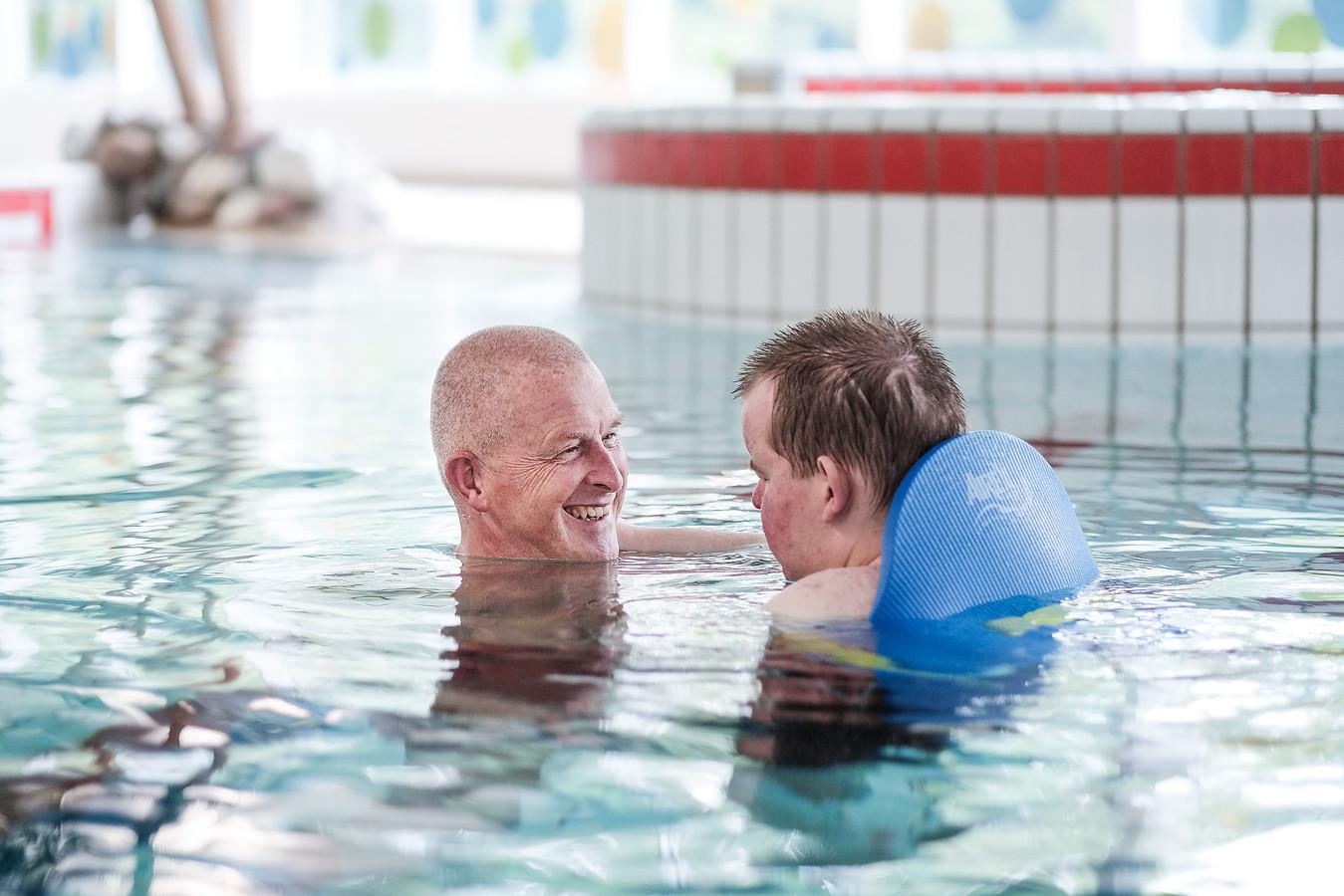 Bert van Horen en zijn zoon in het water.
