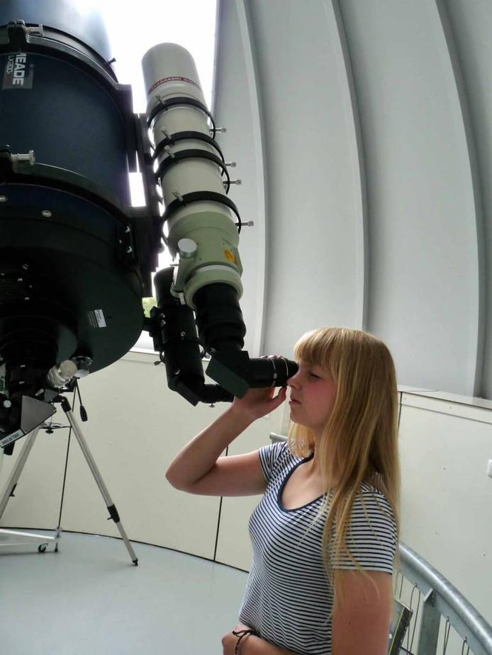 Anna tuurt door een telescoop in de koepel van de sterrenwacht in Nijverdal naar de sterrenhemel.