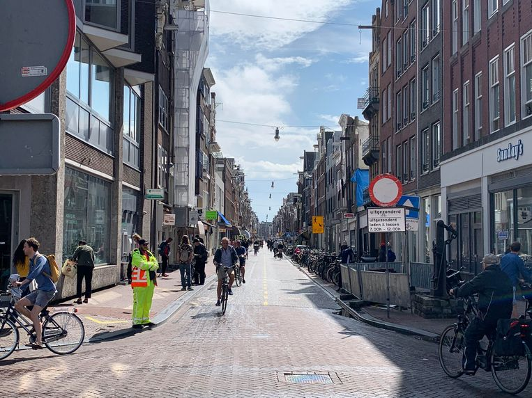 Een verkeersregelaar houdt bij het Haarlemmerplein auto's en scooters tegen. Beeld Jesper Roele