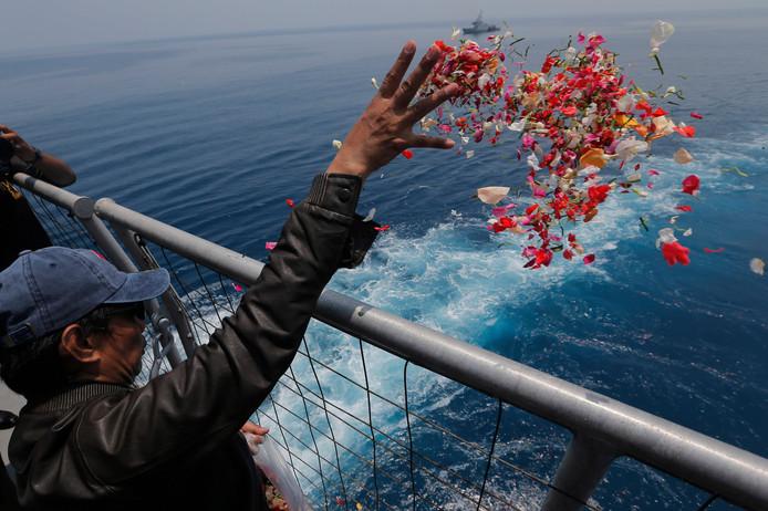 Een familielid van een van de slachtoffers van de crash met de Boeing van Lion Air strooit bloemen in de Javazee op de plaats waar het toestel neerkwam.