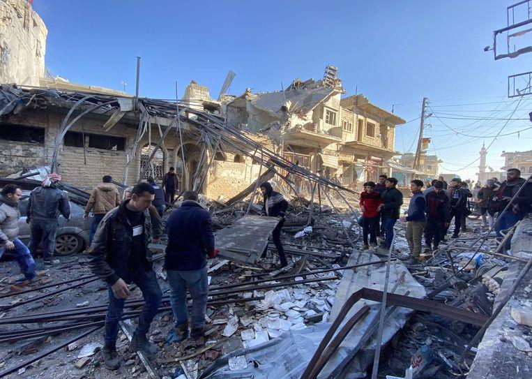 Inwoners van de stad Binnish, in de Syrische provincie Idlib, temidden van verwoestingen als gevolg van een luchtaanval van het Assad-regime.    Beeld AFP