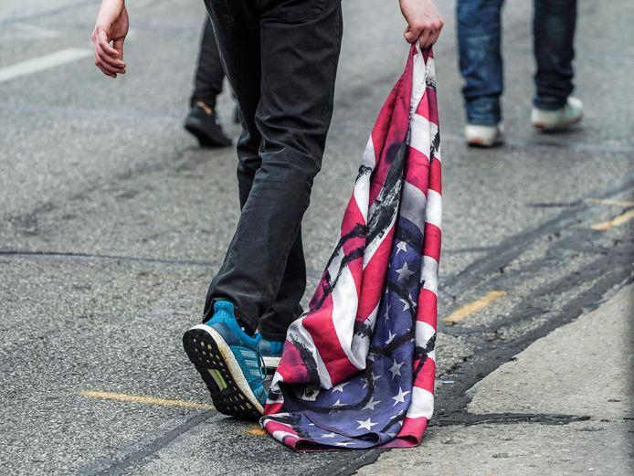 Een demonstrant sleept een Amerikaanse vlag over de grond in Kenosha.