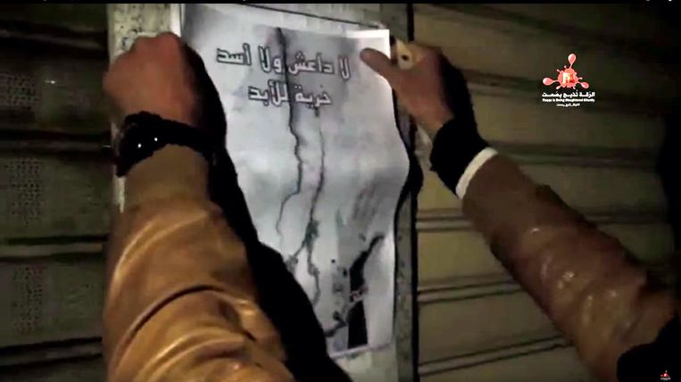 Beeld van video op de website van Raqqa is Being Slaughtered Silently. Activisten van de groep plakken een pamflet op de muur in Raqqa om te protesteren tegen Assad en IS. Beeld .