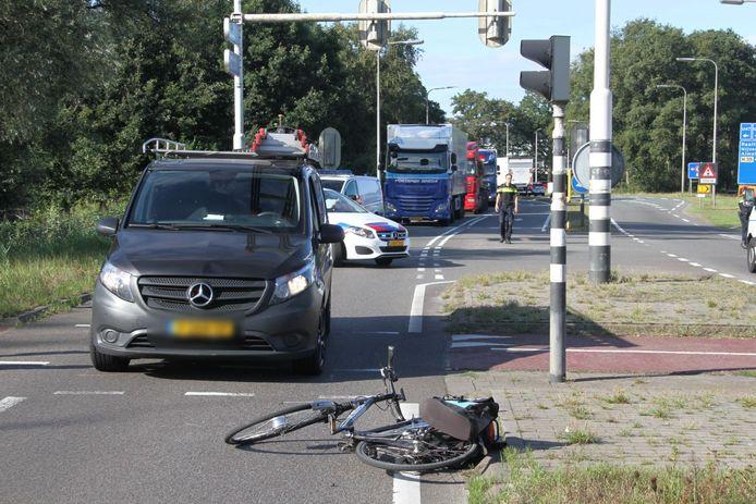 De fiets ligt voor de bedrijfsbus op het asfalt.