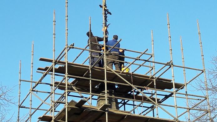 De spits wordt teruggeplaatst op de 11 meter hoge toren.
