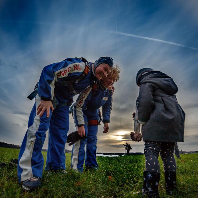 Paul en Tonja Timmermans worden na hun parachutesprong opgewacht door kleindochter Julia (2). 'Wát een zicht, wát een wind, wát een ervaring.'