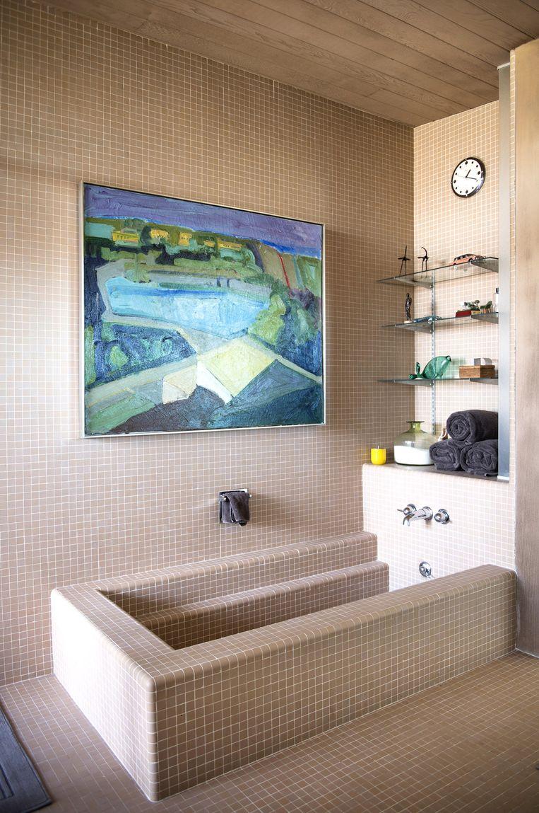 'Het tegeltje in de badkamer is gebruikt in alle toiletten en badkamers in het huis. Het schilderij van Richard Lem is uit de jaren zestig. Ik heb het onlangs gekocht. Het is een gezicht op Silver Lake in Los Angeles.' Beeld Foto Els Zweerink