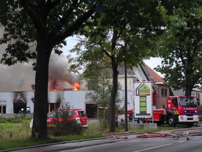 De loods van de winkel staat in lichterlaaie. De vlammen slaan door het dak.