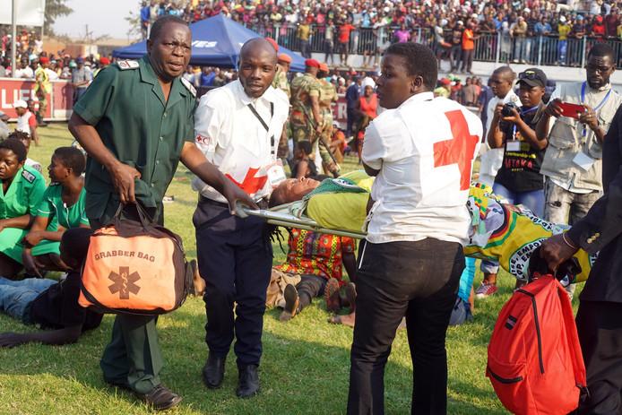 Gewonden worden afgevoerd na gedrang en chaotische taferelen in het Rufaro-stadion in Harare waar het lichaam van oud-president Mugabe ligt opgebaard.