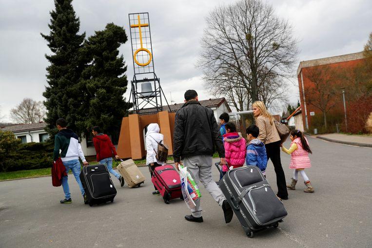 Volwassenen en kinderen arriveren bij een vluchtelingenkamp in Friedland, Duitsland. Beeld Reuters