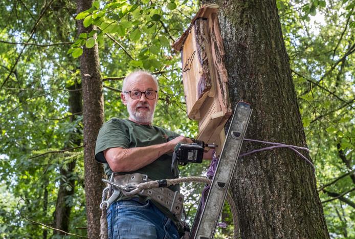 Henk Klaassen hangt in het Avonturenbos de vleermuizenkast op.