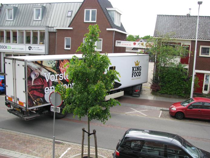 Een vrachtwagen rijdt door de smalle doorgang aan de Tweede Oude Heselaan.