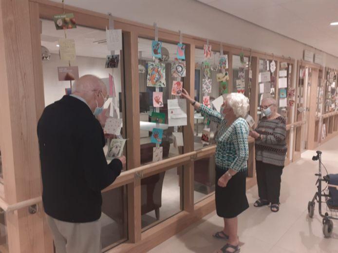 Enkele bewoners van 'de Magnolia' in WZC Sint-Vincentius in Deinze bekijken de kaartjes.