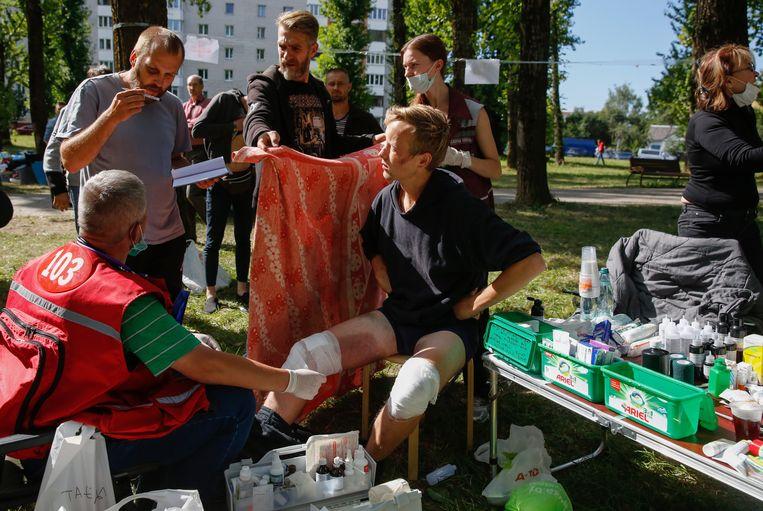 Artsen in Minsk behandelen buiten op straat vrijgelaten arrestanten, die in detentie door de politie zijn mishandeld. De Belarussische oproerpolitie pakte de afgelopen dagen duizenden betogers van de oppositie op.  Beeld EPA