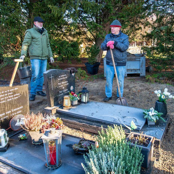 Martien van leeuwen (l) en Cees Gijzen halen het grind weg bij het graf van hun dierbaren.  De begraafplaats krijgt een opknapbeurt.