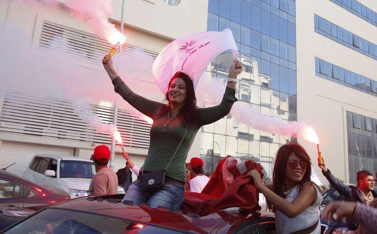 Supporters van de seculiere Nidaa Tounis partij vieren feest op straat. Beeld null