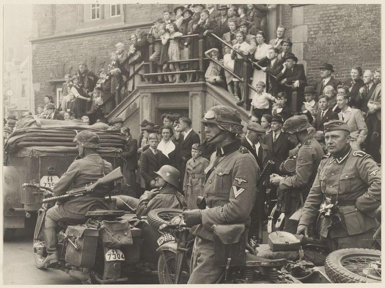 Haarlem, 15 mei 1940. De eerste Duitse troepen komen op de Grote Markt in Haarlem aan. Nieuwsgierige toeschouwers staan op het bordes van het stadhuis. Beeld Adrianus Peperkamp/Noord-Hollands Archief