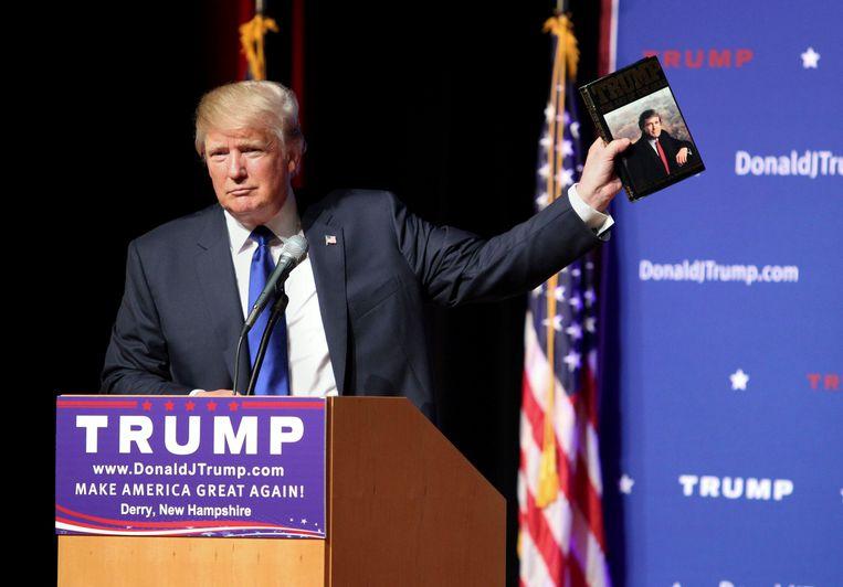 Tijdens een campagnebijeenkomst in augustus 2015 toont Donald Trump het publiek zijn boek Trump: The Art of the Deal. Beeld null