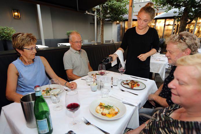 Gastvrouw Loesje Clement voorziet haar gasten van een glas wijn op het terras in de binnentuin van Chocolat.