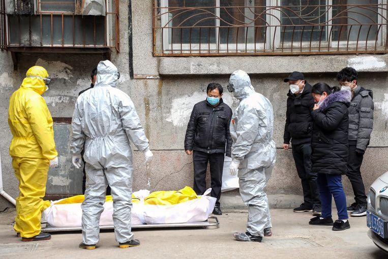 Begrafenisondernemers halen een slachtoffer van het coronavirus op in Wuhan. Beeld EPA