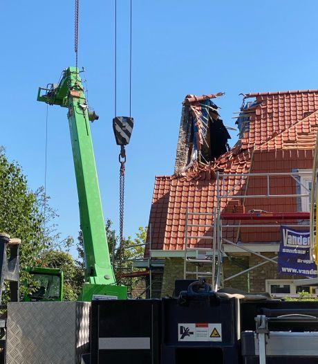 Loodzware machine kantelt tegen dak van villa, met ravage tot gevolg