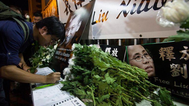 Een man tekent in het condoleanceregister voor Liu Xiaobo. Beeld afp