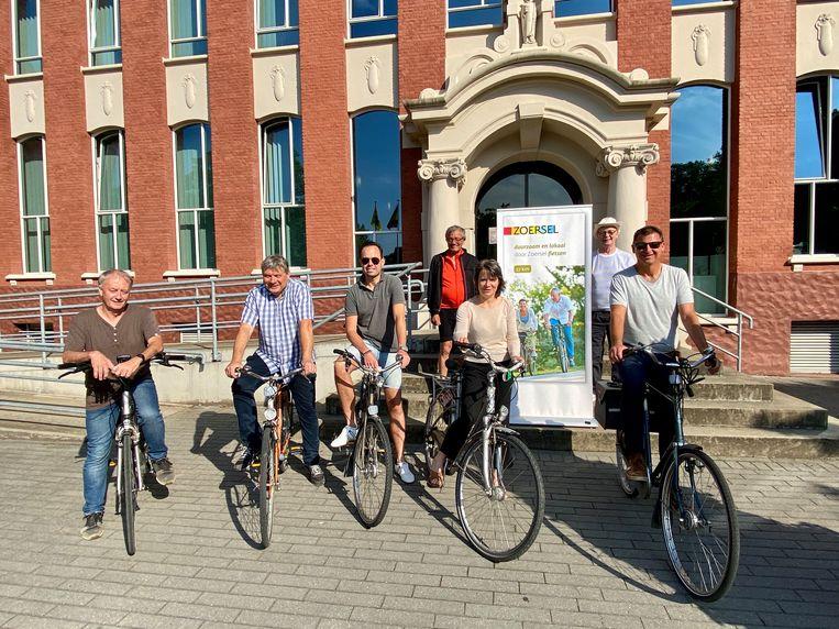 Het schepencollege op de fiets met Patrick Debaere (links) en Marcel De Vos (rechts) op de trappen aan het gemeentehuis