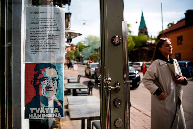 Een poster van Anders Tegnell, hét wetenschappelijke gezicht van de Zweedse aanpak, hangt aan de deur van een restaurant in Stockholm om mensen erop te wijzen dat ze hun handen moeten wassen.