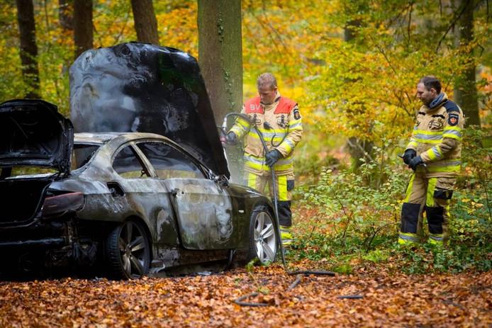 De bij de overval gebruikte BMW werd uitgebrand teruggevonden in een bos bij Olst. foto Stefan Verkerk
