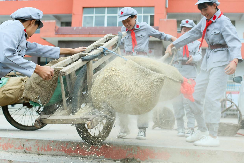 Leerlingen van de Rode Leger School in Yi'nan sjorren aan een houten kruiwagen waarop een zak met graan ligt. De school laat ze de tijden van de stichters van de Volksrepubliek herbeleven. Beeld Elke Scholiers
