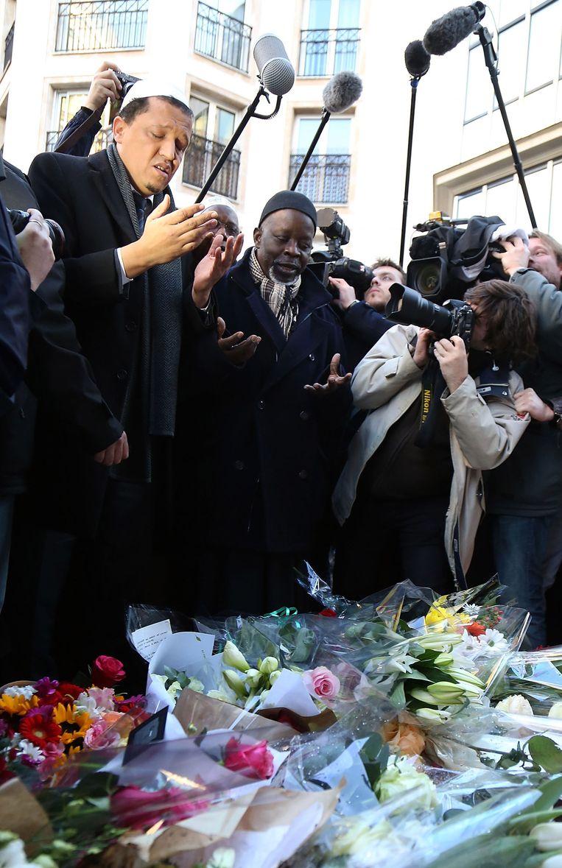Hassen Chalghoumi, imam van de Drancy moskee in Parijs, laat bloemen achter bij het kantoor van Charlie Hebdo. Hij bidt voor de slachtoffers. Beeld getty
