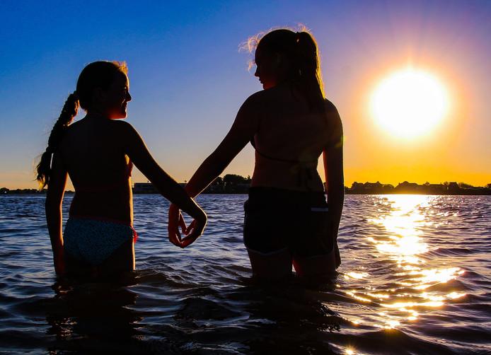 Hun handen haken ineen als ze samen in het water van de Merwede staan. Twee zusjes in de avondzon, nabij een strandje aan de rivier. Silhouetten in gouden licht.