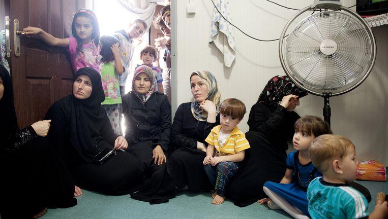 Syrische weduwen zitten in een container in het vluchtelingenkamp in de Turkse grensplaats Kilis. Beeld An Sofie Kesteleyn