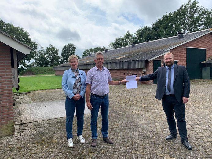 Wethouder Martijn Breukelman overhandigt het sloopbewijs voor 1400 vierkante meter aan pluimveestallen 'coronaproof' aan Gerard en Esther Stroot in Bruchterveld.