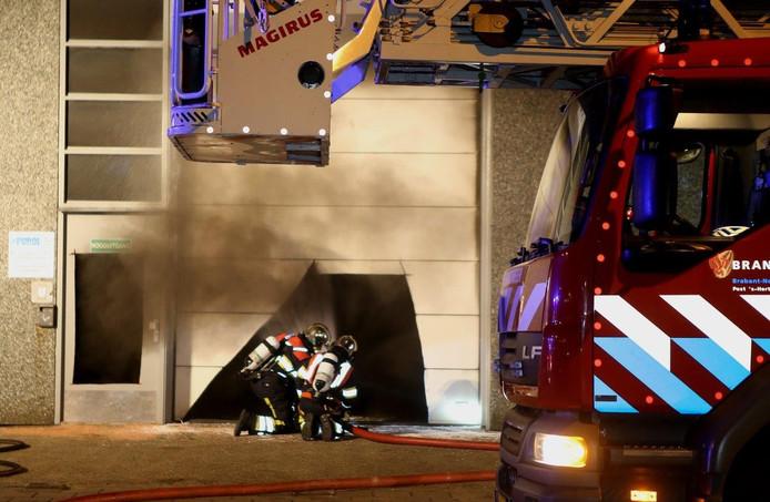 Via een gat in de roldeur heeft de brandweer het vuur gedoofd