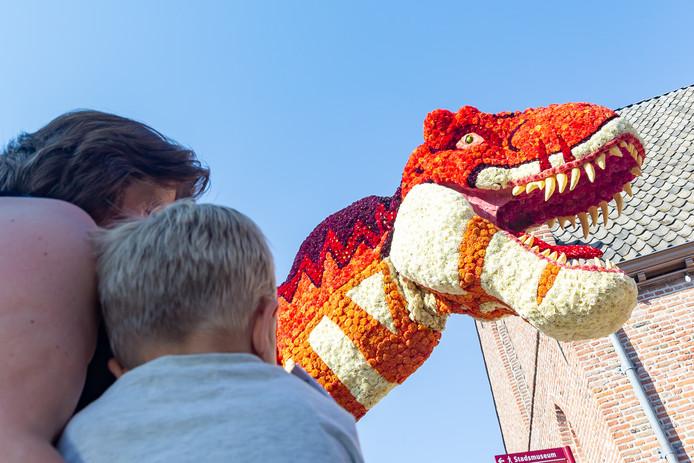 Veilig op de arm, denkt dit jongetje als De Vereniging langs komt met hun enorme dinosaurussen.
