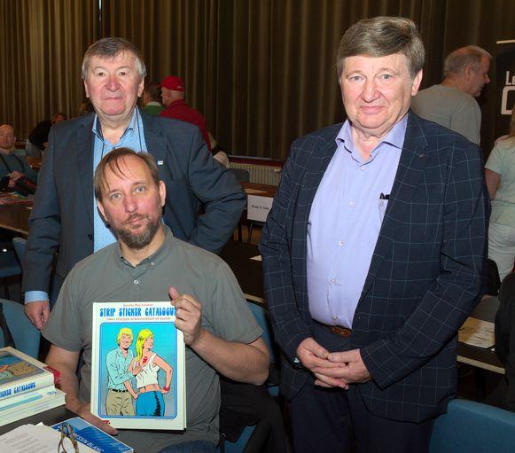 Sascha Van Laeken met zijn nieuwe 'Strip Sticker Catalogus', in het bijzijn van burgemeester Luc De Ryck en Spirit-voorzitter Raoul De Graeve.