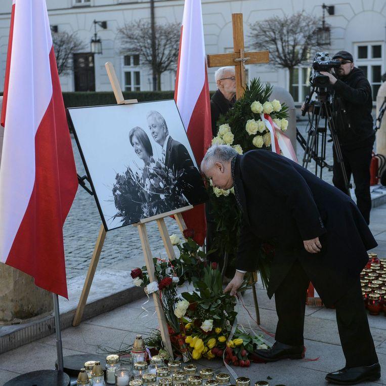 Jaroslaw Kaczynski legt bloemen bij de foto van zijn omgekomen broer en schoonzus. Beeld EPA