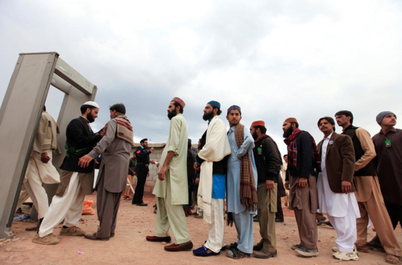 Mannen staan in de rij voor het beveiligingspoortje van de schrijn van Mumtaz Qadri, een radicale moslim die de gouverneur van Punjab doodschoot.