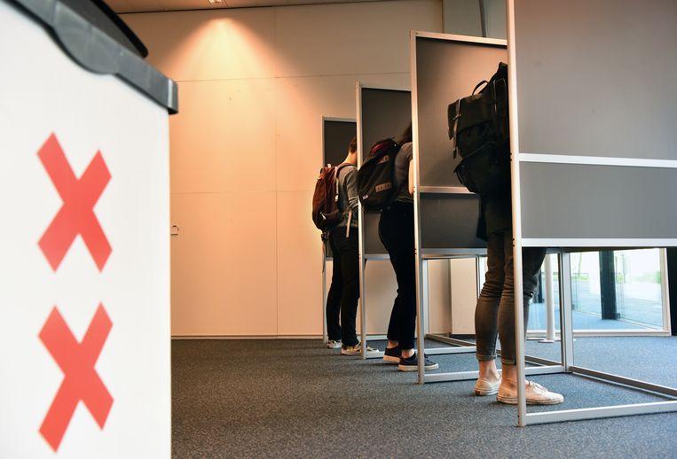 Amsterdamse studenten stemmen vaak net even voor hun college of in een pauze.  Beeld Marcel van den Bergh