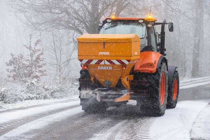 Een strooiwegen strooit zout door de sneeuw bij Het Drielandenpunt in Vaals.
