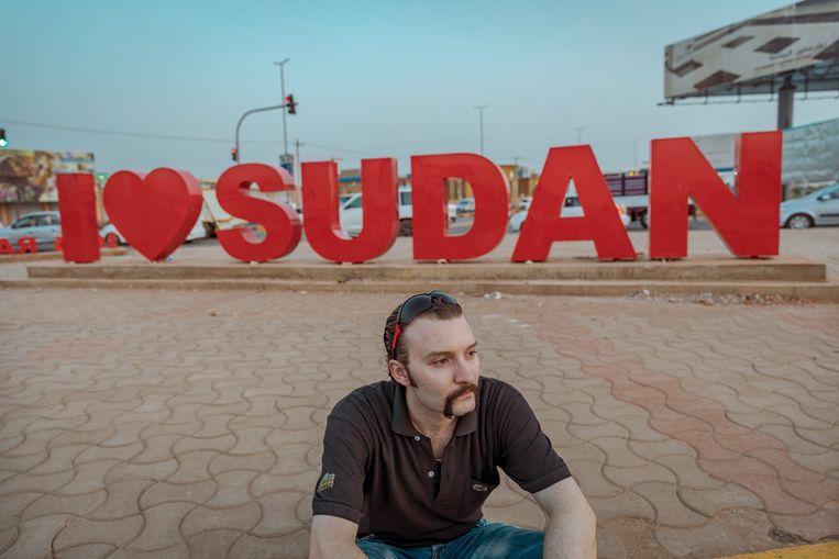 Omar, uit Syrië, op een kruispunt in Khartoum. Achter hem een de woorden 'I love Sudan'. Beeld Sven Torfinn