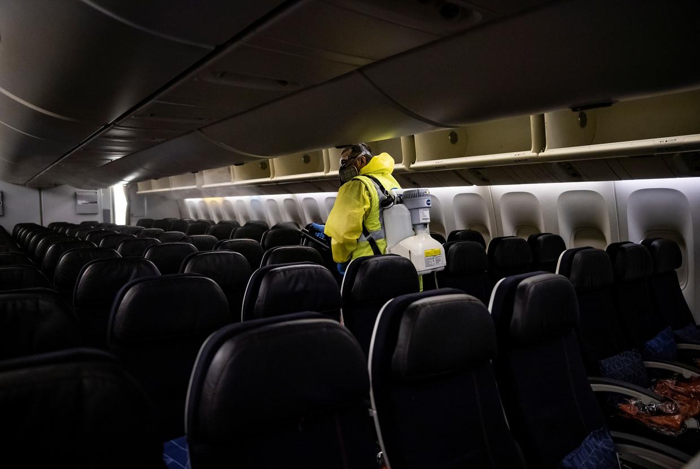Een medewerker van het Charles de Gaulle vliegveld in Parijs maakt een vliegtuig schoon. Beeld REUTERS