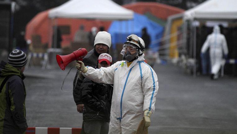 Mensen in beschermende kleding wijzen inwoners van Koriyama de weg naar de plek waar mensen die binnen 20 kilometer van de centrale in Fukushima zijn geweest worden gescand op radioactieve straling. Beeld ap