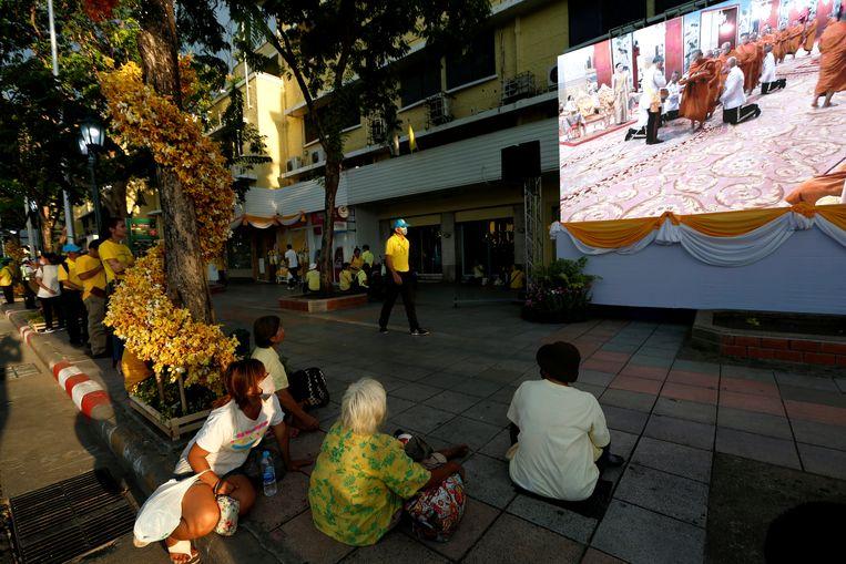 Mensen kijken de live broadcast van de voorbereidingen voor koning Maha Vajiralongkorn's kroning op een straat in Bangkok.  Beeld Reuters / Soe Zeya Tun