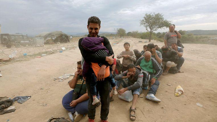 Syrische vluchtelingen wachten bij het Griekse plaatsje Idomeni. Beeld reuters