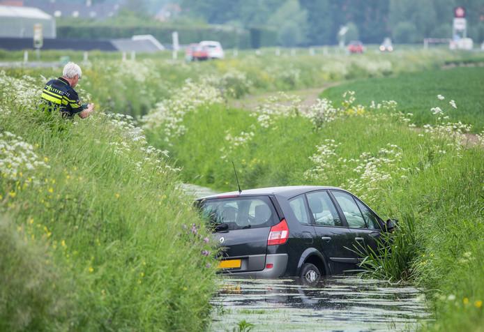 Mevrouw met auto te water langs de Trambaan in Strijen.