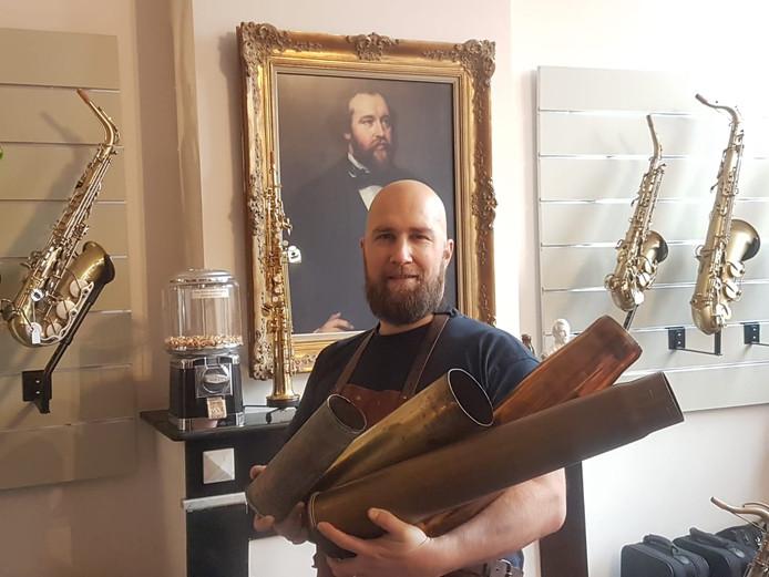 Saxofoonbouwer Karel Goetghebeur met enkele granaathulzen.