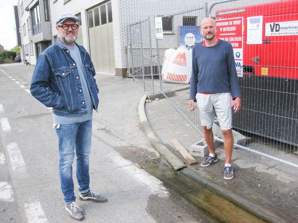 """Koen Roman (Groen) en Steven Bettens (Groen) bij een bouwwerf waar opgepompt water onmiddellijk naar de riool stroomt. """"In periodes van droogte moet dat verboden worden"""", vinden ze."""