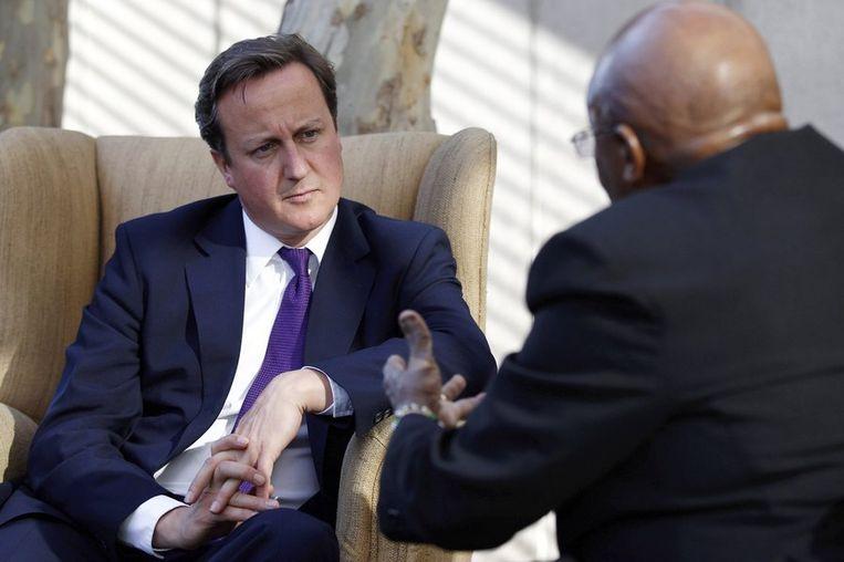 De Britse premier Cameron is op bezoek in Zuid-Afrika. Hij komt dinsdag terug voor een spoedzitting in het Britse parlement. Beeld reuters